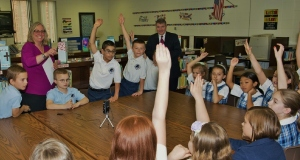Principal with students raising hands for game show for web